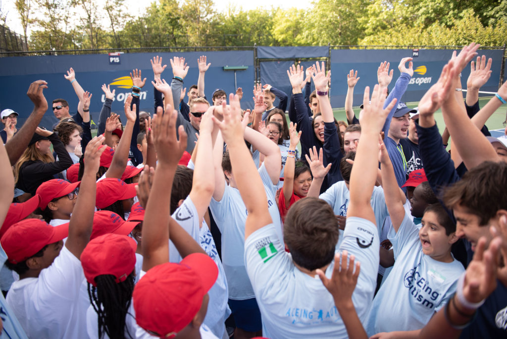 Crowd of kids throwing up their hands in a celebratory manner on the tennis court