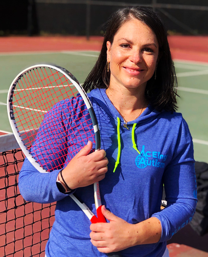 woman holding tennis racquet smiling at camera